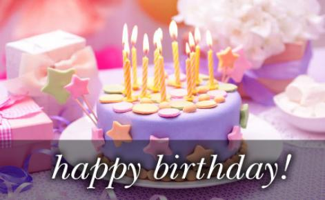 Image of a birthday cake with lit candles and the text