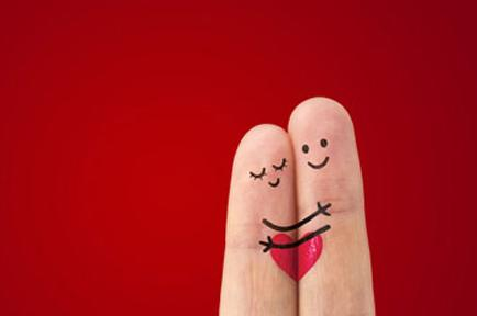 Image of two fingers with drawing of with two stick people hugging