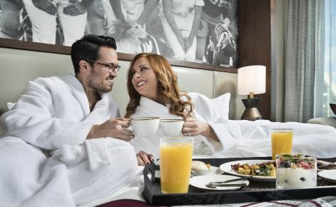 Image of couple eating breakfast in bed