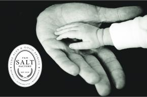 Image of a child's hand in an adults hand with the Salt Factory Pub logo