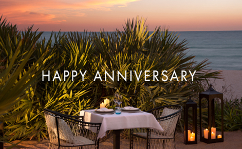 "Gift card image of a table set for two on the beach at sunset with the text ""Happy Anniversary"