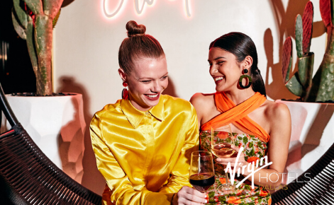 Gift card image of two ladies enjoying a cocktail with the Virgin Hotel Dallas logo