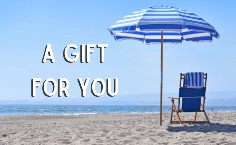 "Gift card image of a deck chair and parasol on the beach with  the text ""A gift For You"""