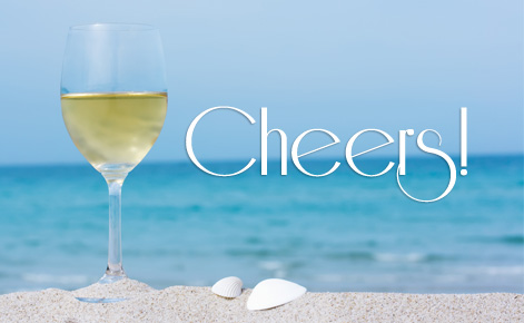 Image of glass of wine on the beach with the text