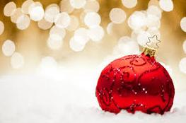 Image of red Christmas ball in front of a sparkly gold background