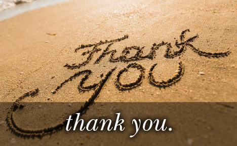 Image of thank you written in the sand with the text