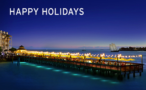 """Gift card image of the pier at night with the seating area all lit up and the text """"Happy Holidays"""""""