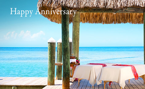 "Gift card image of two spa beds set up next to the beach with the text ""Happy Anniversary"""